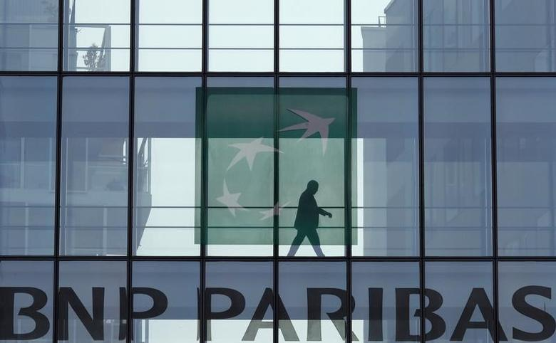 A man is seen in silhouette as he walks behind the logo of BNP Paribas in a building in Issy-les-Moulineaux, near Paris, France, April 5, 2017. REUTERS/Gonzalo Fuentes