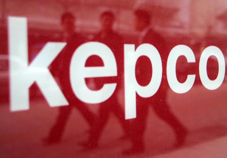 FILE PHOTO: South Koreans are reflected in a company sign for Korea Electric Power Corp (KEPCO) in Seoul February 18, 2005.   REUTERS/You Sung-Ho/File Photo