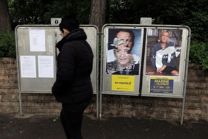 A woman walks past official posters of candidates for the 2017 French presidential election Marine Le Pen of French National Front (FN) political party (R) and Emmanuel Macron, head of the political movement En Marche !, or Onwards !, (L) in Cambrai, France, May 4, 2017. REUTERS/Pascal Rossignol