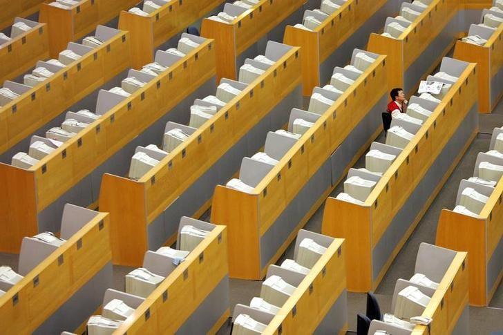 资料图片:2006年7月,上海证交所交易大厅内的一名交易员。REUTERS/Aly Song