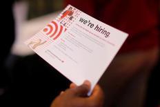 """Pessoa em busca de emprego segura papel com a frase """"Estamos Contratando"""" em uma loja de Boston. 01/05/2017 REUTERS/Brian Snyder"""