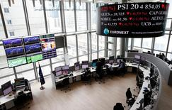 FILE PHOTO: Traders work at their desks in a trading room at the stock market operator Euronext headquarters in La Defense business and financial district in Courbevoie near Paris, June 8, 2016. REUTERS/Gonzalo Fuentes