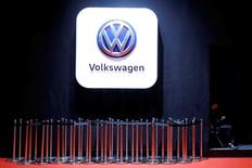 FILE PHOTO: A man uses phone under a Volkswagen logo at the Shanghai Auto Show, in Shanghai, China April 20, 2017. REUTERS/Aly Song