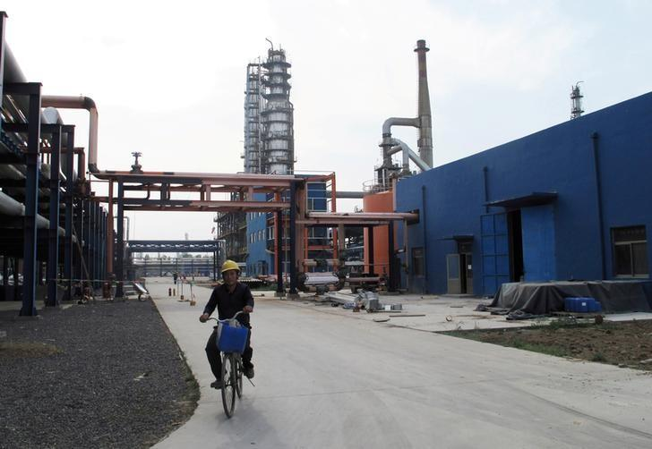 An employee rides a bike on a road near refinery plants of Chambroad Petrochemicals, in Boxing, Shandong Province, China, May 10, 2016. REUTERS/Meng Meng/File Photo