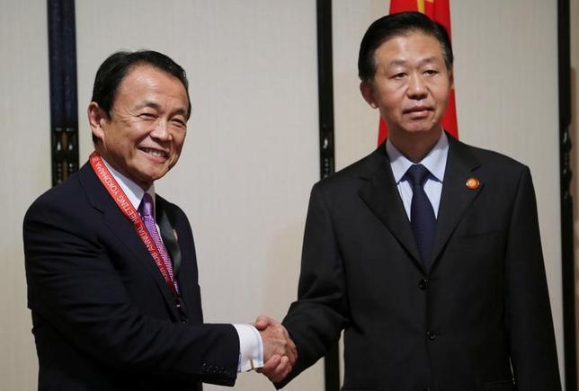 5月6日、日中両政府は、横浜市で開かれているアジア開発銀行(ADB)の年次総会に合わせ、両国の経済金融情勢などについて意見交換する「日中財務対話」を開催した。写真は、握手する麻生財務相(左)と中国の肖捷財政部長。代表撮影(2017年 ロイター)