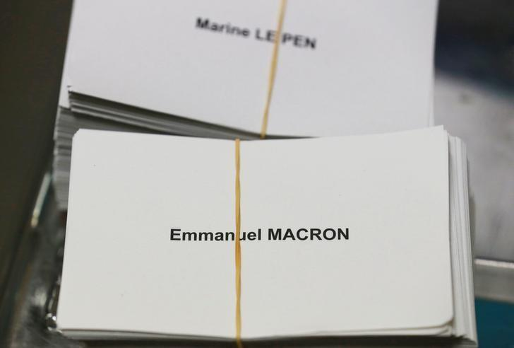 Ballots with the names of 2017 French presidential election candidates Emmanuel Macron (Bottom) and Marine Le Pen are seen near ballot boxes on the eve of the second round of the French presidential election, at a polling station in Tulle, France, May 6, 2017. REUTERS/Regis Duvignau