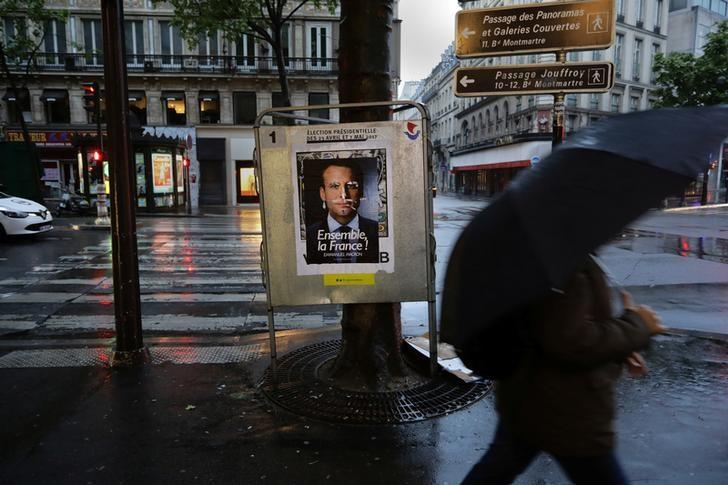 A man walks past an election poster of candidate Emmanuel Macron the day of the French presidential election in Paris, France, May 7, 2017.     REUTERS/Kevin Coombs