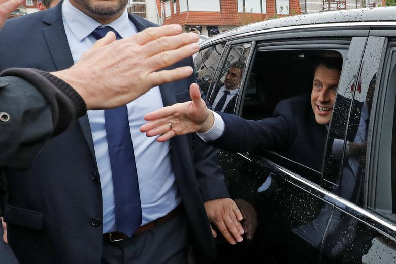 French presidential election candidate Emmanuel Macron, head of the political movement En Marche !, or Onwards ! greets supporters as leaves a polling station during the the second round of 2017 French presidential election, in Le Touquet, France, May 7, 2017. REUTERS/Philippe Wojazer