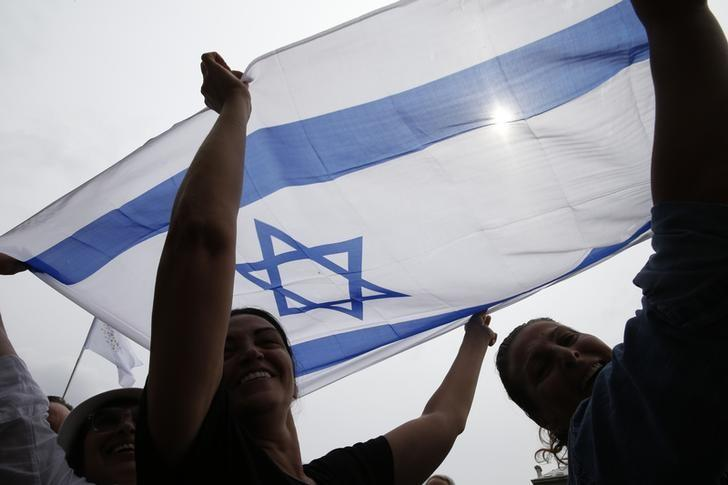 People hold high an Israeli flag on a artificial sand beach at ''Paris Plages'' to show their support  for the ''Tel Aviv on Seine'' event, in Paris, France, August 13, 2015.  REUTERS/Pascal Rossignol/Files