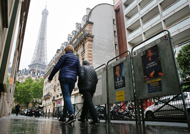 People pass election posters in Paris during the second round of 2017 French presidential election, France, May 7, 2017. REUTERS/Gonzalo Fuentes