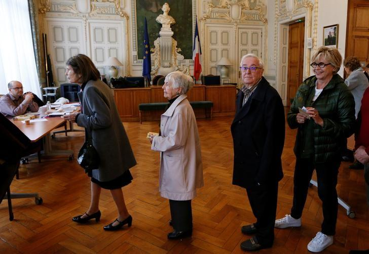 People wait in line to vote in the second round of 2017 French presidential election at a polling station in Lyon, France, May 7, 2017. REUTERS/Robert Pratta