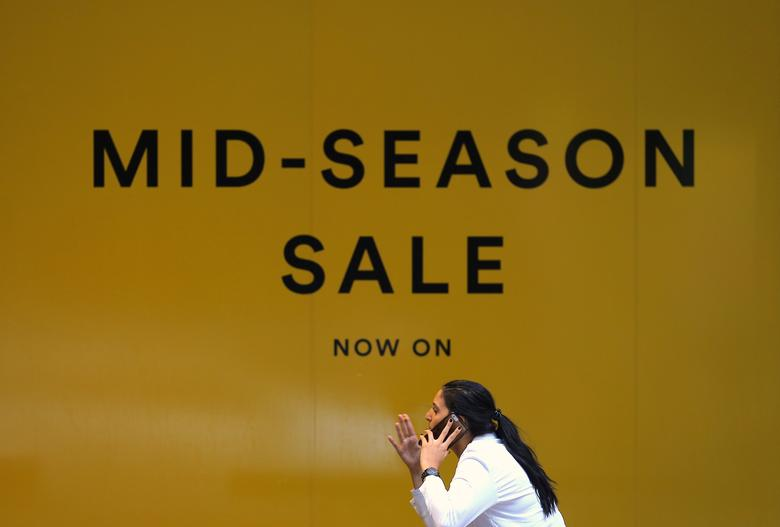 A woman reacts as she talks on her phone in front of a retail store displaying a sale sign at a shopping mall in central Sydney, Australia, April 12, 2017. Picture taken April 12, 2017.     REUTERS/Steven Saphore