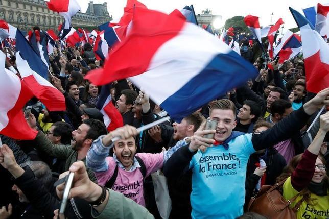 5月7日、2つの世論調査結果によると、来月に行われる仏国民議会(下院)選の第1回投票では、大統領選で勝利したマクロン氏が率いる政治運動とその連立政党が支持率で首位となっている。写真は大統領選でのマクロン氏の勝利を祝う支持者ら。パリで撮影(2017年 ロイター/Christian Hartmann)