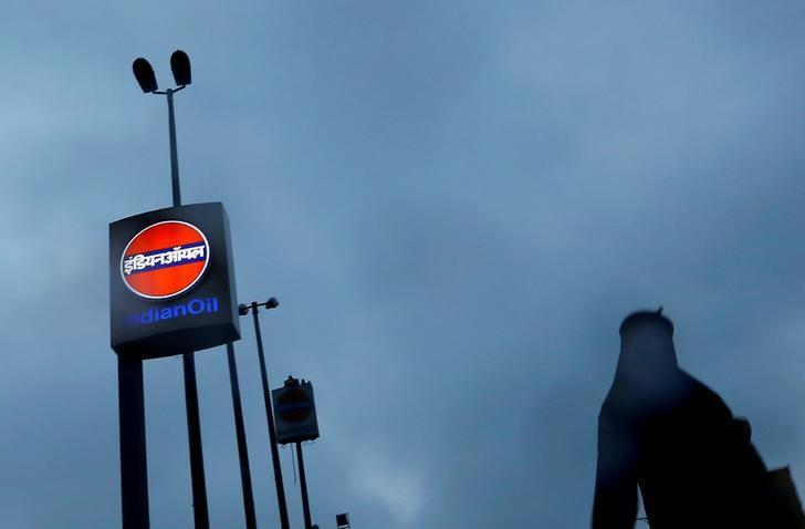 FILE PHOTO: A woman walks past a logo of Indian Oil outside a fuel station in New Delhi, India, August 29, 2016. REUTERS/Adnan Abidi/File photo