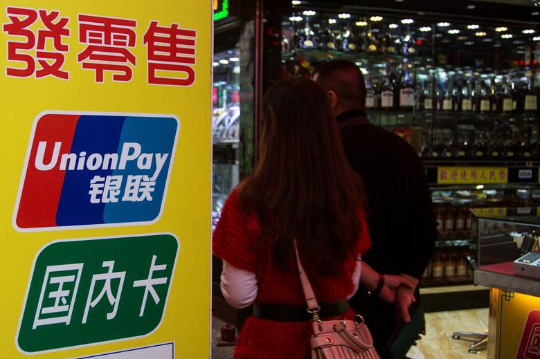 FILE PHOTO - Chinese visitors walk past a sign for China UnionPay outside a pawnshop in Macau, in this picture taken November 20, 2013. Picture taken November 20, 2013.    REUTERS/Tyrone Siu/File Photo