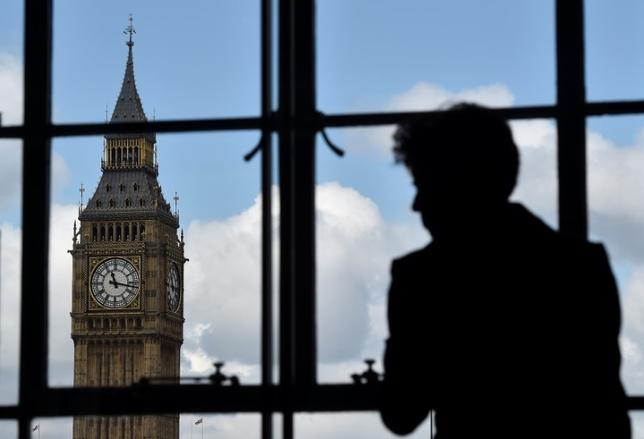 A woman looks out of a window at the Big Ben clock tower in London, Britain, April 26, 2017. REUTERS/Hannah McKay