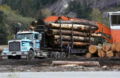 FILE PHOTO: A worker checks a truck with a load of logs at Sqomish Forestry LP in Squamish, British Columbia, Canada on April 25, 2017.  REUTERS/Ben Nelms/File Photo