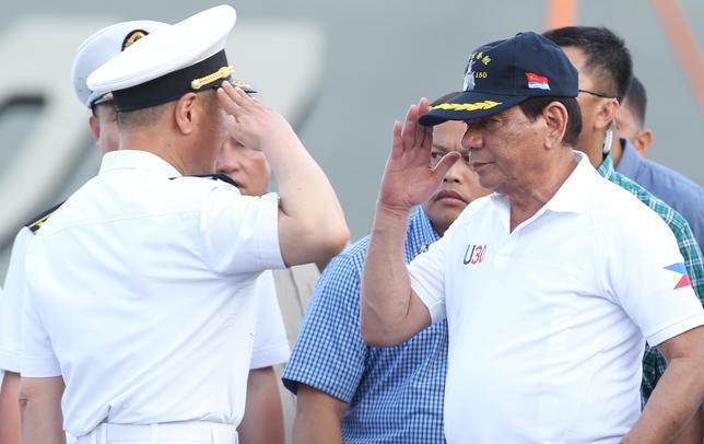 5月2日、中国政府の勢力圏に引き寄せられる国々がアジア全域で増えつつある。写真は1日、フィリピンのダバオに入港した中国海軍艦艇を視察するフィリピンのドゥテルテ大統領(2017年 ロイター/Lean Daval Jr)