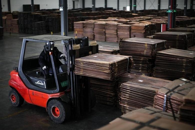 资料图片:2012年3月,上海洋山港附近一处仓库,一名工人在搬运铜板材。REUTERS/Carlos Barria