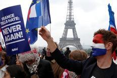 Los costes de endeudamiento en toda la zona euro subieron el martes ya que el decisivo resultado de las elecciones presidenciales francesas permitió a los inversores cambiar el foco hacia las perspectivas de un recorte de los estímulos monetarios del BCE. En la imagen, varias personas reunidas cerca de la torre Eiffel de París celebran el resultado electoral en Francia el 8 de mayo de 2017.  REUTER/Pascal Rossignol