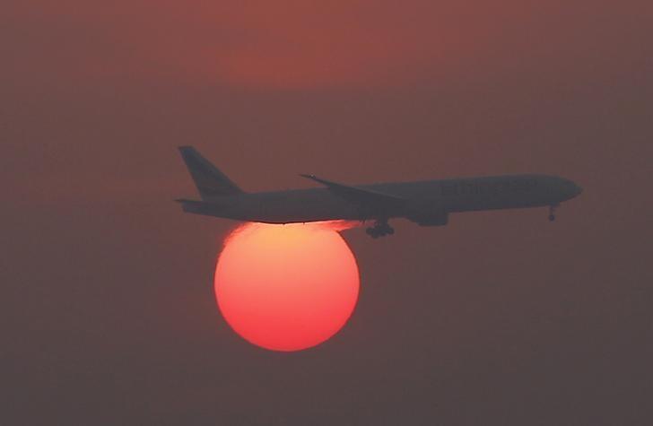 资料图片:2016年3月,北京首都国际机场,一架飞机飞过日暮时分的天空。REUTERS/Kim Kyung-Hoon