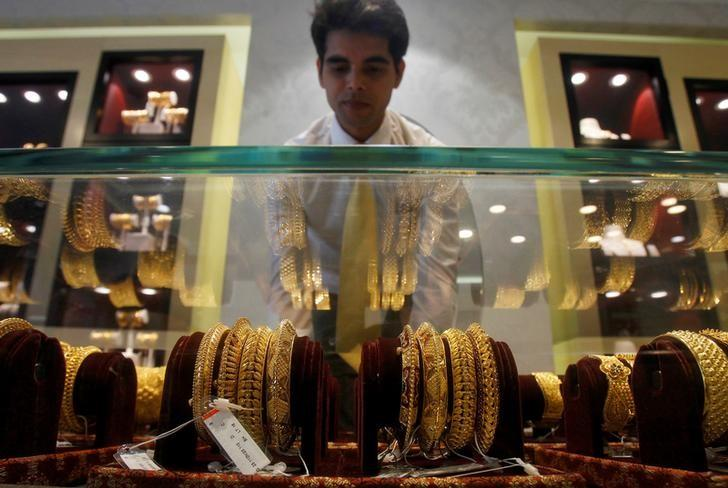 A salesman arranges gold bangles in a display case inside a jewellery showroom on the occasion of Akshaya Tritiya, a major gold buying festival, in Agartala, April 28, 2017. REUTERS/Jayanta Dey/Files
