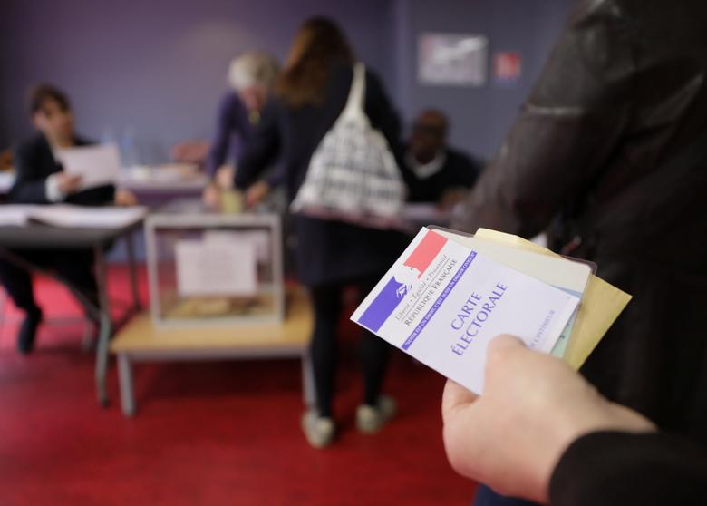 FILE PHOTO: A person holds a voter's registration card before voting in the second round of 2017 French presidential election at a polling station in Paris, France, May 7, 2017. REUTERS/Eric Gaillard