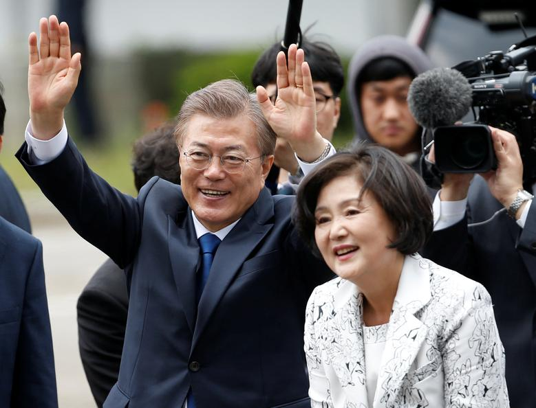 South Korea President Moon Jae-in and his wife Kim Jung-sook wave to neighborhood residents as they arrive at the presidential Blue House in Seoul, South Korea May 10, 2017. REUTERS/Kim Kyung-Hoon