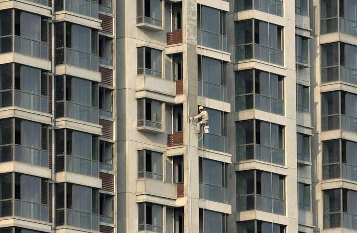 资料图片:2009年11月,南京,一名工人在粉刷未竣工的住宅楼外墙。REUTERS/Sean Yong