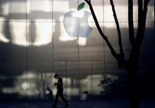FILE PHOTO: A man uses his phone as he walks past an Apple store in Beijing, China on April 25, 2017. REUTERS/Thomas Peter/File Photo