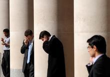 Impiegati della City parlano al cellulare all'ingresso della Borsa di Londra.    REUTERS/Toby Melville/File Photo