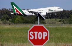 Un velivolo di Alitalia atterra a Fiumicino, in primo piano un cartello di 'stop'.   REUTERS/Max Rossi