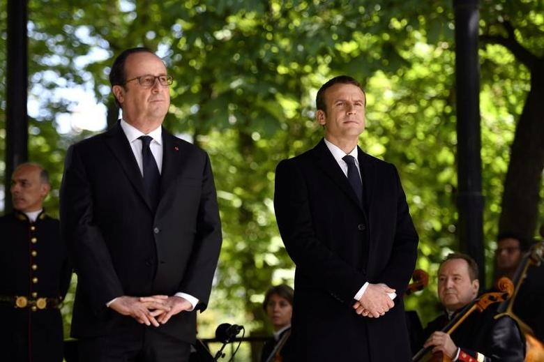 Outgoing French President Francois Hollande (L) and President elect Emmanuel Macron attend a ceremony to mark the anniversary of the abolition of slavery and to pay tribute to the victims of the slave trade at the Jardins du Luxembourg in Paris, France,  May 10, 2017. REUTERS/Eric Feferberg/Pool