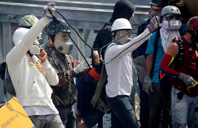 Opposition supporters use a giant sling shot to throw a ''Poopootovs'', a bottle filled with feces, which is a play on Molotov, during a rally against President Nicolas Maduro in Caracas, Venezuela, May 10, 2017. REUTERS/Carlos Garcia Rawlins