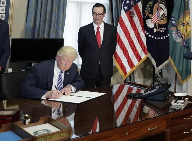5月10日、11─13日にイタリアのバーリで開催される主要7カ国(G7)財務相・中央銀行総裁会議で、欧州諸国や日本、カナダは保護主義などを巡るトランプ米大統領の政策の方向性について理解を深めることを期待している。写真はトランプ米大統領(左)とムニューシン米財務長官(右)。ワシントンで4月撮影(2017年 ロイター/Kevin Lamarque)