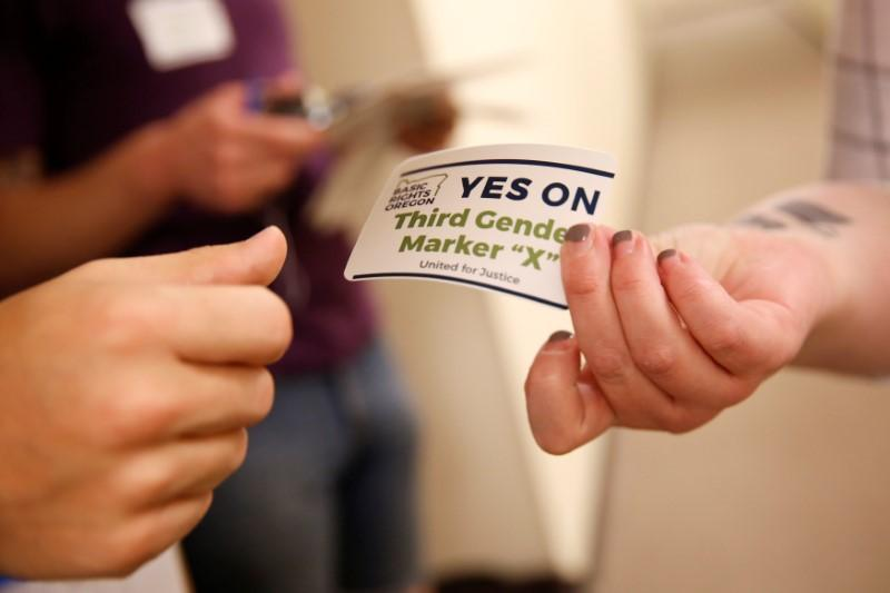 An employee of the advocacy group Basic Rights Oregon hands out stickers during an Oregon Driver and Motor Vehicle department public hearing on the rights ...