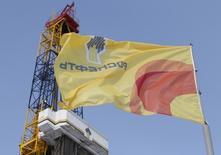 Флаг с логотипом Роснефти на Сузунском месторождении к северу от Красноярска 26 марта 2015 года. Российская государственная нефтяная компания Роснефть столкнулась с трудностями в попытке завершить крупнейшее для себя зарубежное приобретение - покупку Essar Oil India за $12,9 миллиарда, поскольку несколько индийских кредиторов Essar пока не одобрили сделку, сказали источники, близкие к переговорам. REUTERS/Sergei Karpukhin
