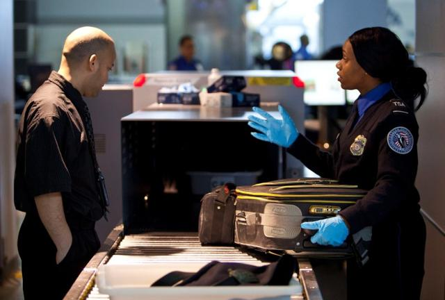 FILE PHOTO - A Transportation Security Administration (TSA) security agent takes a traveler's luggage for a second security check at John F. Kennedy Airport in New York, U.S. on February, 29, 2012.    REUTERS/Andrew Burton/File Photo