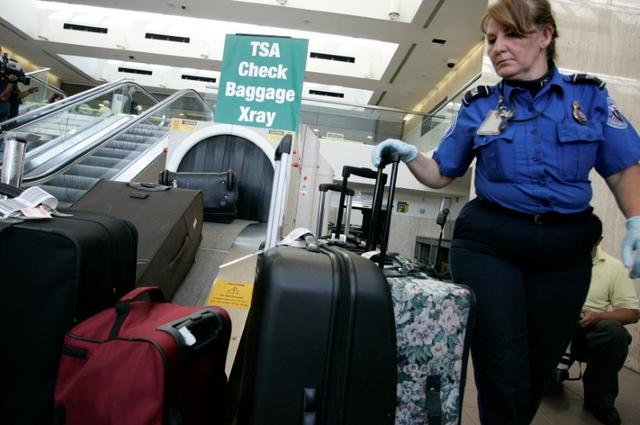 FILE PHOTO - A TSA worker loads suitcases at the checked luggage security screening station at Los Angeles International Airport in Los Angeles, California, U.S. on September 7, 2011. REUTERS/Jonathan Alcorn/File Photo