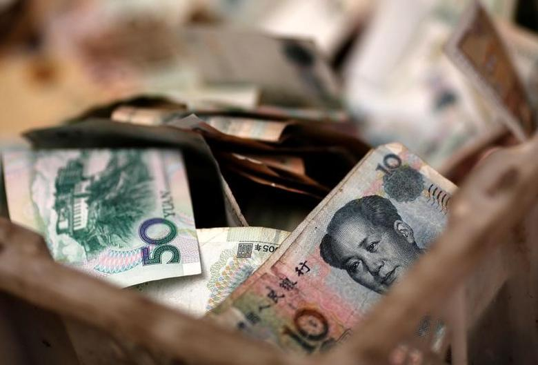 Chinese banknotes are seen at a vendor's cash box at a market in Beijing February 14, 2014.     REUTERS/Kim Kyung-Hoon/File Photo