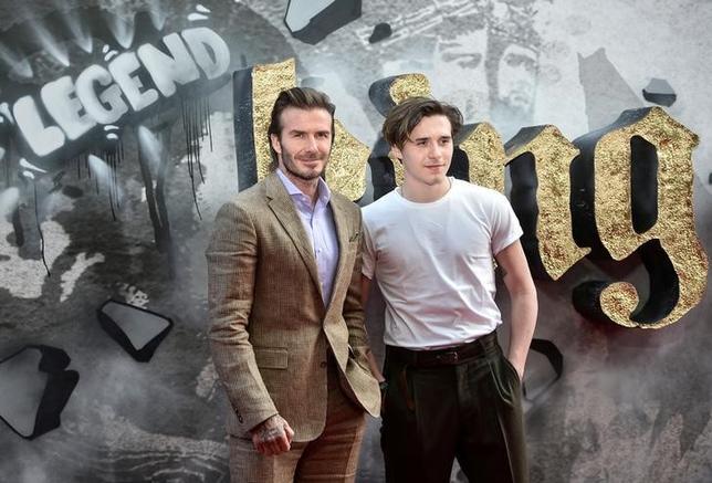 5月10日、サッカーの元イングランド代表主将デービッド・ベッカムは、ガイ・リッチー監督の新作映画「キング・アーサー」(日本公開6月17日)にカメオ出演、監督はその演技を高く評価した。写真はロンドン開催のプレミアに息子のブルックリン(右)と登場したベッカム(2017年 ロイター/Hannah McKay)