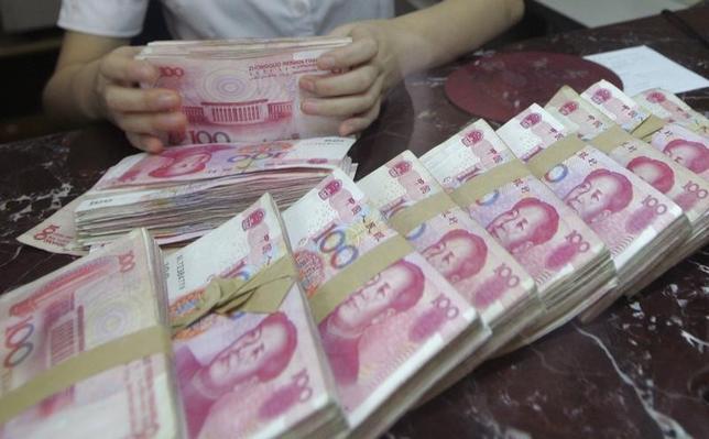 5月12日、関係筋によると、中国銀行業監督管理委員会(CBRC、銀監会)は今週、「影の銀行」(シャドーバンキング)に対する取り締まりの一環として、銀行の新たな業務に関する緊急のリスク審査に着手した。写真は人民元紙幣を数える銀行員。2012年7月遼寧省で撮影(2017年  ロイター)