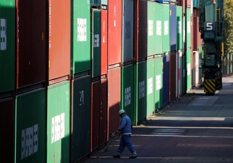 A worker walks between shipping containers at a port in Tokyo, Japan, March 22, 2017. Picture taken March 22, 2017. REUTERS/Issei Kato