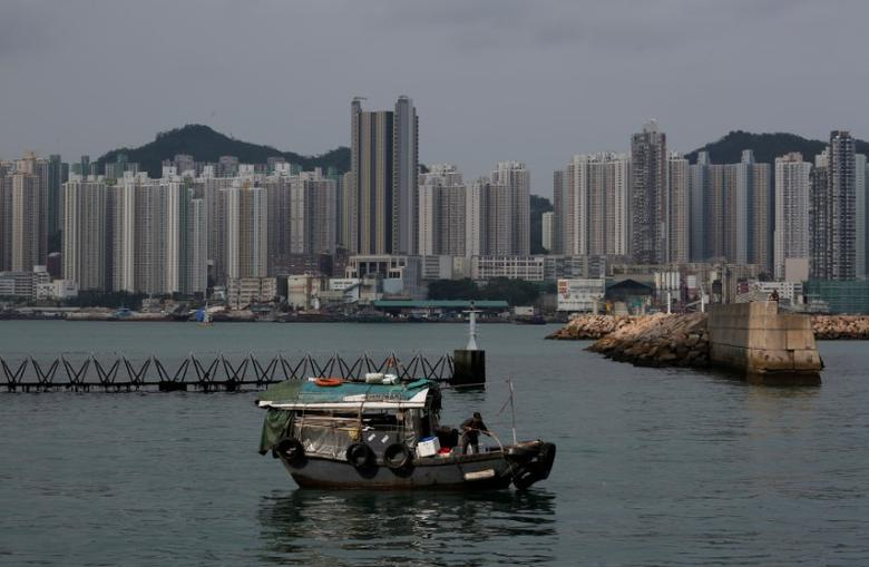 A boat sails in front of private and public housing blocks in Hong Kong, China April 28, 2017.      REUTERS/Bobby Yip
