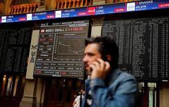 El selectivo de la bolsa española subía ligeramente en la media sesión del viernes tras registrar el jueves su peor jornada desde que comenzó el año, y con el mercado aún pendiente de los resultados empresariales. En la imagen, un hombre habla por teléfono en la Bolsa de Madrid, el 24 de junio de 2016.  REUTERS/Andrea Comas