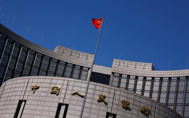 FILE PHOTO: A Chinese national flag flutters outside the headquarters of the People's Bank of China, the Chinese central bank, in Beijing, April 3, 2014. REUTERS/Petar Kujundzic/File Photo
