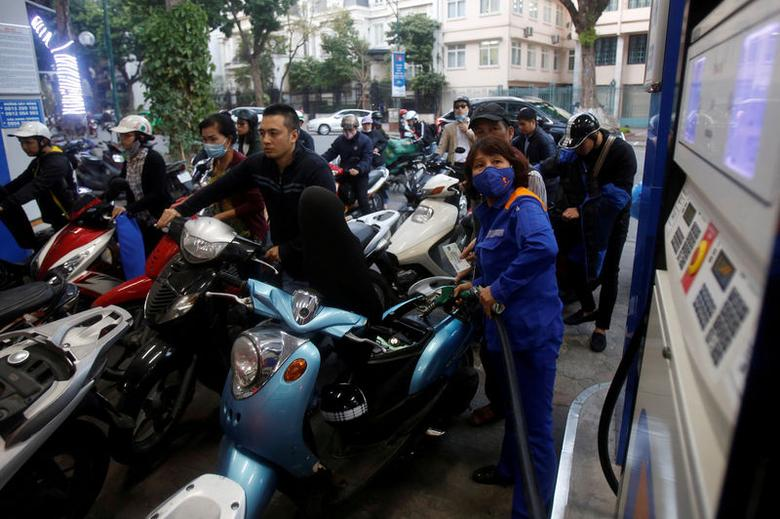 FILE PHOTO: An employee pumps petrol for clients at a petrol station in Hanoi, Vietnam December 20, 2106. REUTERS/Kham/File Photo