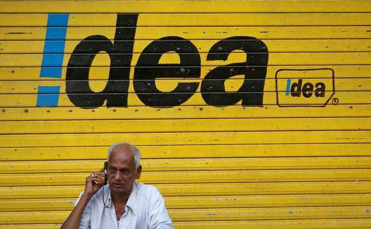 FILE PHOTO: A man speaks on his mobile phone as he sits in front of a shop displaying the Idea Cellular Ltd's logo on its shutter in Mumbai, India, April 28, 2014. REUTERS/Danish Siddiqui