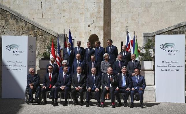 5月13日、麻生太郎財務相は、イタリア南部バリで開かれたG7財務相・中央銀行総裁会議後に記者会見し、保護貿易への懸念が「かなり解消した」との見方を示した。13日撮影の同会議出席者の集合写真(2017年 ロイター/Alessandro Bianchi)
