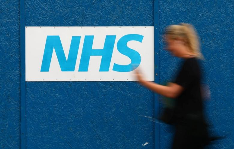 A woman passes an NHS sign at The Royal London Hospital in London, Britain May 13, 2017. REUTERS/Neil Hall